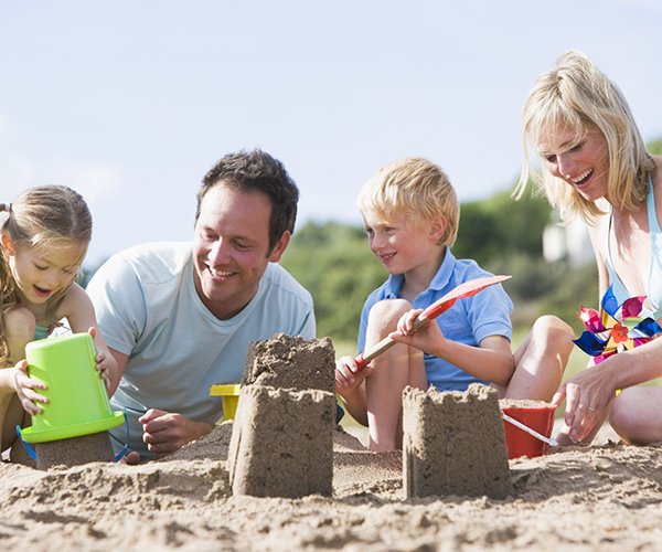 Family on beach making sand castles smiling