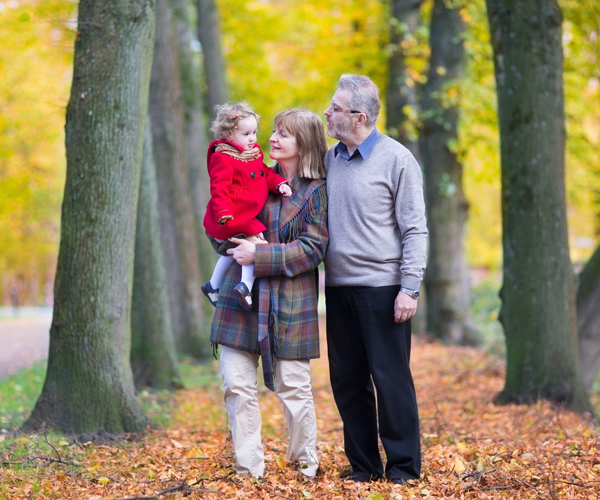 Happy family with a cute toddler girl walking together in a beautiful autumn park with colorful yellow trees